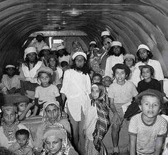 """Image of Yemenite families escaping to Israel in Operation Magic Carpet. 1922, Yemen reintroduced an Islamic law requiring Jewish orphans under age 12 be forcibly converted to Islam.  In 1947 Muslim rioters engaged in a bloody pogrom killing 82 Jews and destroying Jewish homes. In 1948 the false accusation of blood libel led to looting of Jewish homes. Virtually the entire Yemenite Jewish community - almost 50,000 - escaped Yemen between June 1949 and September 1950 in Operation """"Magic Carpet."""""""