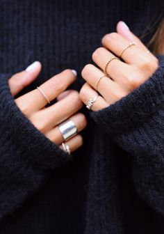 Rings on every finger styled with a cozy black sweater.