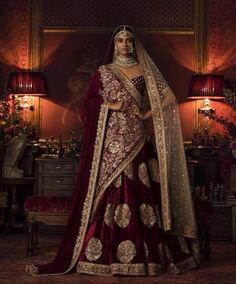 This maroon color bridal lehenga is in silk velvet embroidered with fully zardozi work. Dupatta is in gold colour net fabric with embroidered edges and sequins butties inside. Blouse is also fully embroidered. Velvet shawl completes the look of this bridal lehenga with heavily embroidered pallu at one side.