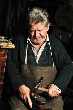 Elderly man, shoemaker repairing old shoe in his workshop Stock Photo