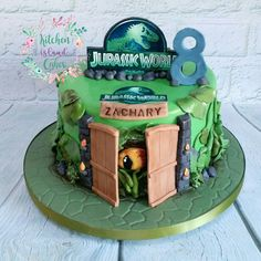 A jungle green dinosaur cake featuring peering dinosaur eye and inspired by Jurassic World Birthday Cake Maker, Park Birthday, Birthday Cake Girls, Birthday Star, Dinosaur Cakes For Boys, Dinosaur Birthday Cakes, Jurassic World Cake, Jurassic Park, Cake Designs For Kids