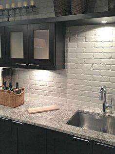painted white brick backsplash with black cupboards