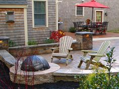 Fire Pit Design Ideas: This circular fire pit was cleverly built right into the retaining wall, which is perfect when you get up close to the heat.  From DIYnetwork.com