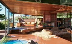 In John Lautner's 1947 design, the swimming pool extends into the living room, and the sofa wall swings open.