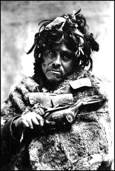 Auk shaman, Alaska, ca. 1900. Formal portrait of shaman in ceremonial dress, holding carved amulet   necklace and a raven rattle; his hair contains ermine pelts.