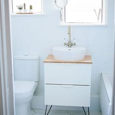 Scandinavian style bathroom. White bathroom with wood accents. IKEA sink with hairpin legs. white subway tile with white grout