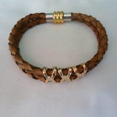 Pulseira feita em couro trançado com retalhes dourado e fecho em imã.