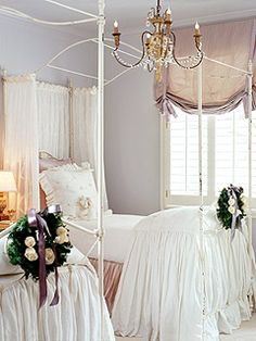 Bedroom with two beds adorned with white skirted duvets and green wreaths.