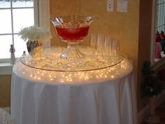 "Take a round table and cover it with a cloth, take 5 or 6 short glasses (I used votive holders) and place them around the table upside down (these are the lifts that support your glass top). Place strands of  ""icicle"" lights, then place the round glass on top."