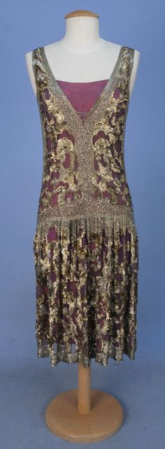 ADAIR PARIS BEADED TULLE OVERDRESS, 1920's. Sleeveless purple tulle with deep V-neck and back decorated with crystal bugle beads at neck, sides, waist and hem and allover abstract pattern of shaped metallic sequins and beads, dropped waist, skirt gathered in front, side slits.