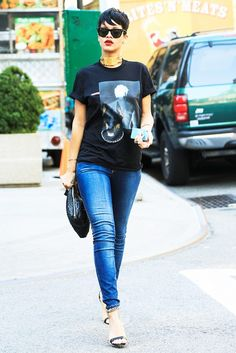 Rihanna wears her pixie cut with a graphic black t-shirt, blue skinny jeans, chain ankle strap heels, an oversize clutch and statement gold choker