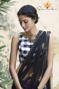 This lehenga comes with a black and white plaid top, black/pink floral raw silk skirt and a black soft net dupatta.