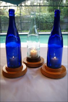 "Handcrafted Wooden Stand Single Wine Bottle Candleholder - Made with a repurposed 750 ml wine bottle. Great for home decor or wine bar decor. The color of the glass adds an ambiance great for an indoor table centerpiece, mantel display, wine bar, or a patio or porch area. The bottle sits on a 3/4 "" (+/-) wood base with wooden feet. Each bottle fits into its own individual stand. This is a great hurricane lantern because the wind won't blow these candles out."