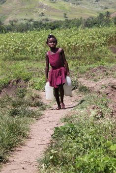A girl collects water in Belanje, Haiti, while her community's well is been under construction.