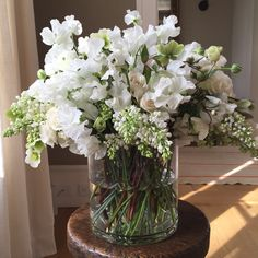 My dream bouquet – all-white sweet peas, ranunculus, lilacs, and hellebores, with a few green leaves that set off the white flowers beautifully.