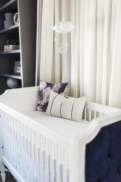 The style is in the details! This Beverly crib from Newport Cottages has tufted end panels in navy velvet. And the cute Moon and Stars mobile is from Baby Jives.