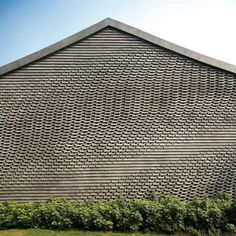 The masonry courses alternate at varying depths to create a play of light and shadow across the wall surface // Lanxi Curtilage by Archi-Union Architects