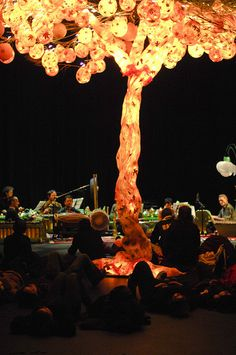 Winter Solstice Lantern Festival Round House Vancouver BC- The Tree of Light (chicken wire/ tissue paper/ hollowed out balloon lanterns as leaves) Recently, the secret Lantern Society have placed musicians in the room, with this tree, that set a spiritual ambiance- you can see the people on the floor enjoying the groove. Art in this room also includes enormous replicas of flowers created from wire and tissue that are pretty impressive