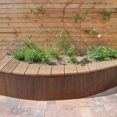 De cortenstalen slingerbank, niet alleen het verbindende element, maar ook de blikvanger van deze tuin bevat ook twee plantvakken met vrolijke planten.