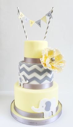Elephant themed chevron baby shower cake by Catisserie, Toronto.   Three tier yellow and grey cake with pennant banner.