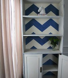 Then, on the bookshelf's inside back wall, Fischer added blue chevron stripes before lightly distressing and sealing the finished product.   - CountryLiving.com