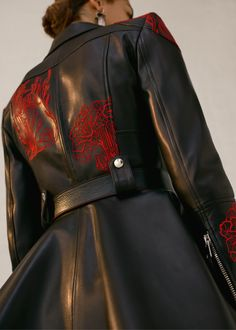 A black peplum perfecto jacket is finished with crimson British Art Nouveau-inspired embroideries. From the Alexander McQueen Autumn/Winter 2018 pre-collection.