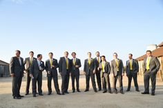 grey suits with yellow ties for groomsmen, but more modern slim fit suits...