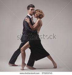 Well-dressed retro couple dancing tango over grey studio background - stock photo