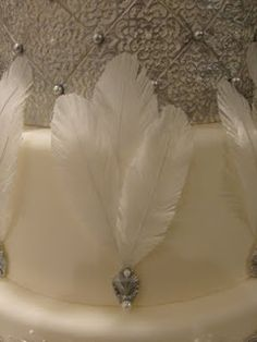 "Here is a short tutorial on how to make edible feathers: You'll need edible wafer paper (sometimes referred to as ""rice paper""), white 28 gauge wire, pearl dust, and clear piping gel."
