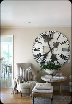linen covered chair with huge metal clock perfect for a farmhouse