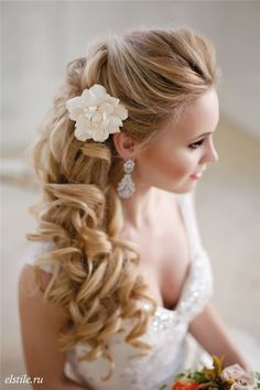 half up half down long cur;ly wedding hairstyle with flower