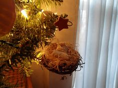 """1 1/2"""" sm grapevine wreath, filled w/ straw like packaging stuff. Baby Jesus is a scrap of cross stitch fabric, muslin or wht burlap. His head is a sm wood-working """"plug"""". Add pink cheeks + 2 Sharpie dot eyes. Glue him in fabric & tie w/ raffia. Paint a sm wood star yellow, & hot glue on 6"""" of pretty stiff wire. Curl it around a pencil, then bend it to shape. Slide it thru the wreath & dab w/ hot glue. Hangs,  sits on table, or use as package toppers on brown kraft paper gifts w/ burlap…"""