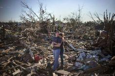Oklahoma City, EE. UU., 21 de mayo de 2013. Una pareja se abraza sobre los restos de su casa familiar en el suburbio de Moore, al sur de Oklahoma City, tras el paso de un tornado encuadrado en la segunda categoría más fuerte. Tocó tierra a una velocidad de más de 300 kilómetros por hora y dejó 24 muertos y 13.000 viviendas destruidas. Foto: Reuters.