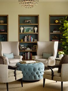 delightful sitting area with the wingbacks, blue tufted ottoman, and nicely contrasted built-ins.