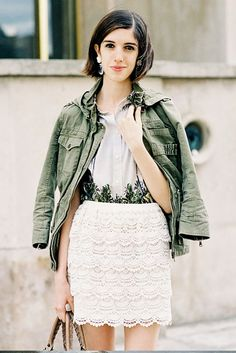An olive army jacket is draped over a button down blouse and lace skirt.