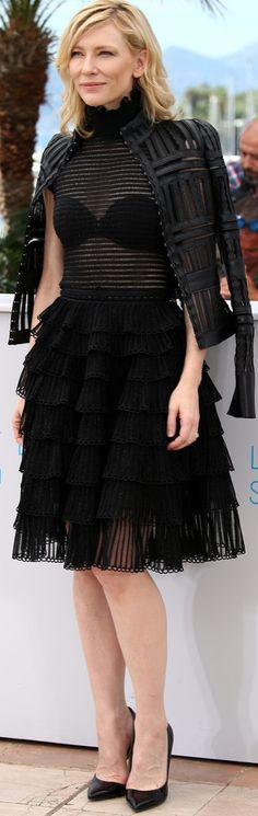 Cate Blanchett let her black bra shine through the sheer bodice of her tiered high-neck Alexander McQueen dress and covered her shoulders with a cutout leather jacket.