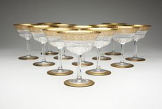 Twelve St. Louis 'Thistle Gold' sherbets ::  20th century, each with etched mark 'Cristal / St Louis / France', each of cut and etched clear crystal with a thistle-shaped bowl, with gilt foliate scroll borders to rim and foot, 12 pcs - est: $1200/1800