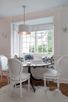Super chic, bright and light breakfast nook by Tiffany Eastman. Love the beautiful millwork on the walls and the detailed pelmet boxes recessed into the bay window banquette. Louis XVI side chairs, contemporary shaded pendant and delicate mirrored sconces add a bit of French flair.