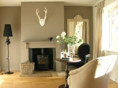 Snug with Farrow & Ball Charleston Grey accent wall. Chair by MADE.COM. Stove Aga