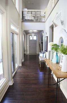 Light and bright hallway with dark handscraped oak floors and chrome swing-arm sconces.