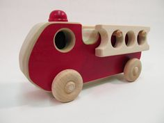 Cute wooden toy fire engine truck. The light is the fire fighter's helmets The…