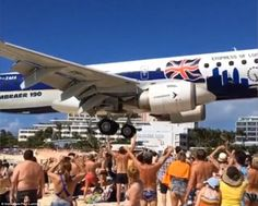 Seemingly closer than normal, the plane's wheels look like they could be touched by the people on Maho Beach