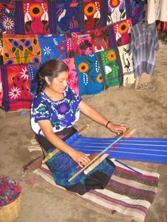 Indigenous Mexican woman weaving on a back-strap loom. Behind her are fabrics she's woven, then embroidered by hand on top of the weaving. Not sure if she is Purèpecha from Michuacàn, or Oaxacan.