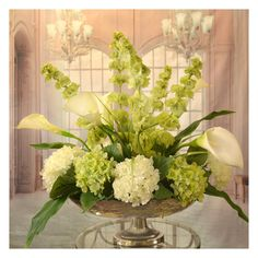 White Calla Lilly and Bells of Ireland Silk Floral Centerpiece in Silver Bowl - Clean, crisp white silk calla lilies, Bells of Ireland, white and green silk hydrangeas arranged in a hammered, silver-toned metal pedestal vase. Our silk design provide Artificial Flower Arrangements, Vase Arrangements, Artificial Flowers, Creative Flower Arrangements, Hotel Flower Arrangements, Dining Room Table Centerpieces, Elegant Centerpieces, Centerpiece Ideas, Silk Flower Centerpieces