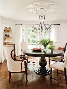 simple take on traditional chandelier. cool orange accents in this room, too. love the table/chairs