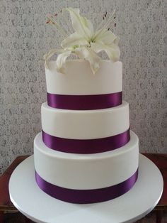 Three tier wedding cake with sugarpaste lilies, lovely purple ribbon. http://www.hbweddings.co.nz/all-listings/Cakes%20/console/cindy-s-cakes.html