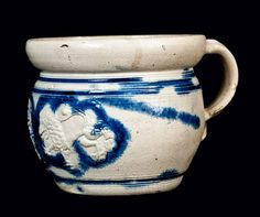 Diminutive Westerwald Stoneware Chamberpot, 17th century, ovoid form with heavily-tooled shoulder and tall, curving rim, decorated with molded lions with crowns flanking a seal containing a shield with stars. Surface decorated with cobalt highlights.