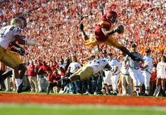 <p>USC running back Reggie Bush jump over UCLA defender Marcus Cassel and into the end zone for a touchdown. Bush's spectacular season earned him the 2005 Heisman Trophy, but the award was later stripped because Bush had received illegal benefits during his time with the Trojans. </p>