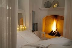 beautiful bedroom space...ledge for candles, fireplace, white sheers & white bedding...