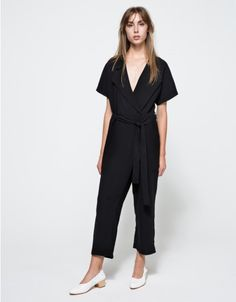 From Stelen, a lightweight flowing short sleeve jumpsuit in black. Features low v-neckline, collar, detachable waistband, square front pockets, belt loops, back pocket, blind hem stitch, full length and relaxed fit throughout.   • Lightweight short slee